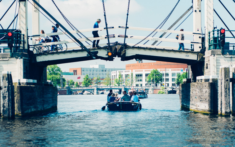Mensen varen in huurboot over amstel amsterdam